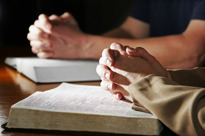 bigstock-Praying-Hands--Bibles-2744390