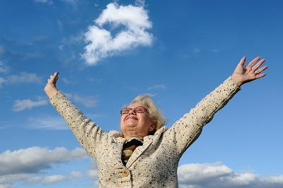 Happy senior lady with hands out stretched against blue sky