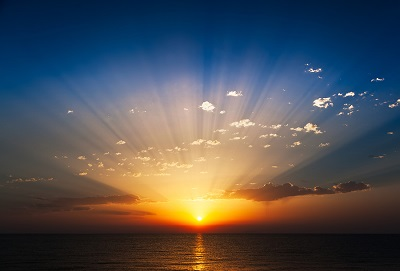 Perfect sunrise on the sea, with radiant rays of sun over a warm