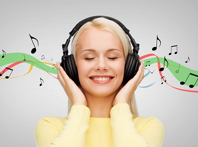 music and technology concept - smiling young woman with closed e