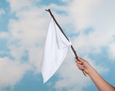 Clouds and female hand waving with a white flag to surrender