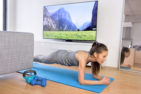 Living room fitness workout - girl doing plank exercises to exer