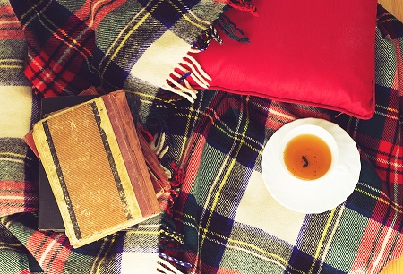 Woolen plaid cup of tea old books red pillow on wooden backgroun