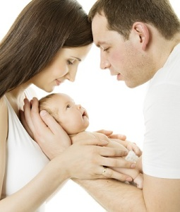 Parents And Baby. Family Mother, Father And Newborn Kid Over Whi