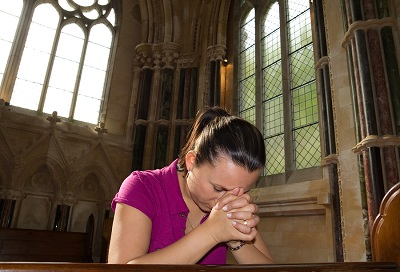 Young woman praying in the church