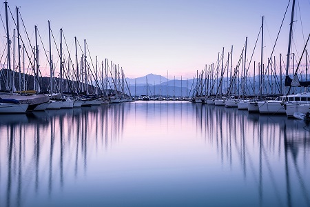 Large yacht harbor in purple sunset light, luxury summer cruise,