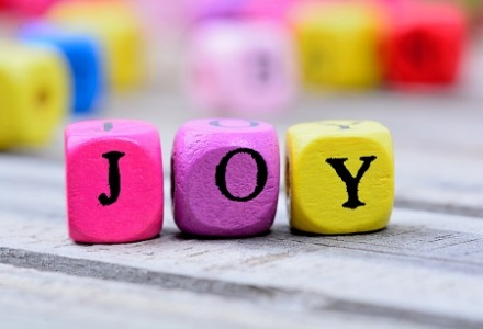 Joy word on gray wooden table closeup